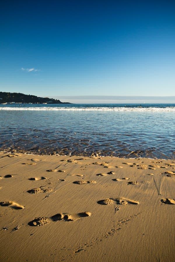 Vue sur la plage sablonneuse avec des traces de pieds et l'Océan Atlantique avec le ciel bleu dans le coucher du soleil photos stock