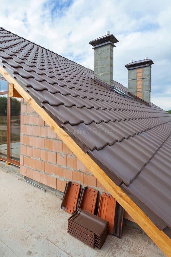 Vue sur le nouveau toit carrelé avec des cheminées de deuxième étage d'une nouvelle maison images stock