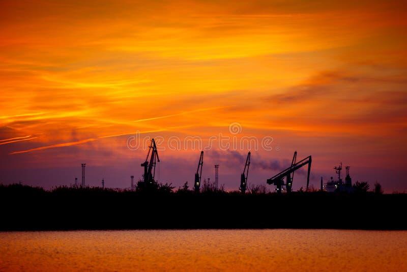 Vue sur le port maritime avec des grues au coucher du soleil Panorama de soirée du port de cargaison image stock