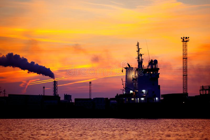 Vue sur le port maritime avec la silhouette de bateau au coucher du soleil Panorama de soirée du port de cargaison images libres de droits