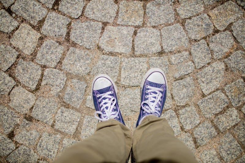 Vue sur les chaussures en caoutchouc et la rue de brique photo stock