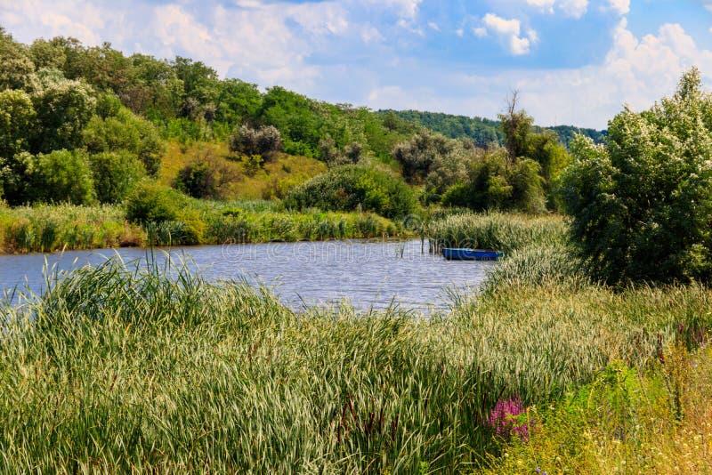 Vue sur un lac calme avec le vieux bateau de pêche en bois en roseaux près d'un rivage photos stock