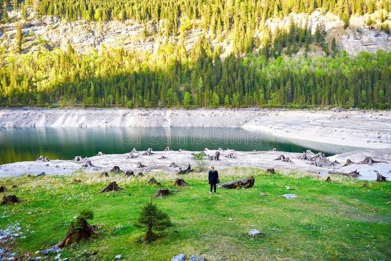 Vue surréaliste unique de lac Vorderer Gosausee avec la femme sur le fond Vue splendide de l'eau, de tranquilité et de tronçons photographie stock libre de droits