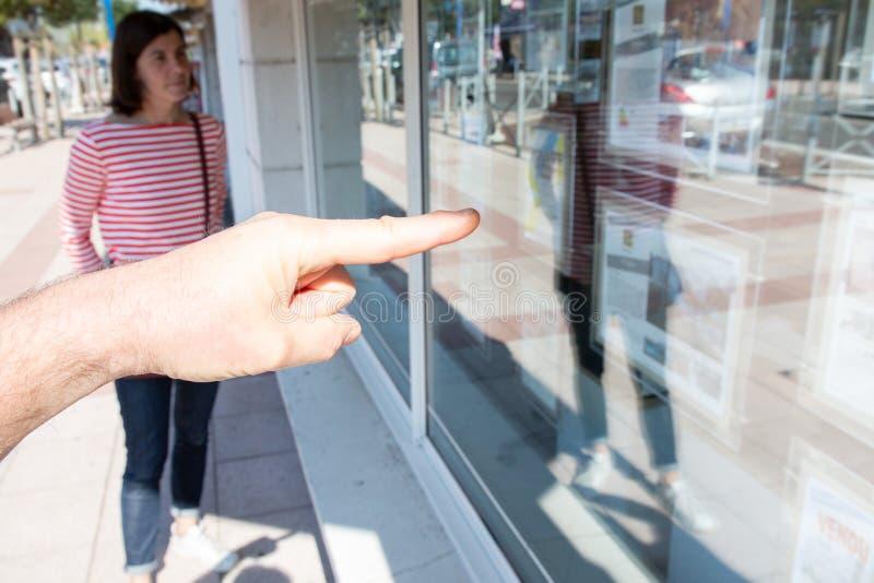 Vue trouble d'un jeune couple regardant l'affichage de fenêtre l'agent de fenêtre de bureau d'immobiliers photo libre de droits