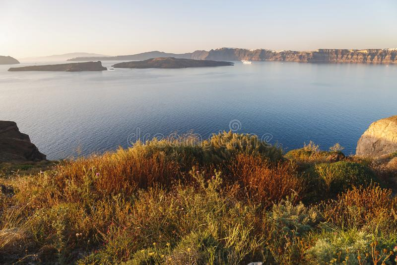 Vue unique de mer à l'île volcanique Nea Kameni, caldeira, au Fira et à l'Imerovigli, avant coucher du soleil, Santorini, G image libre de droits