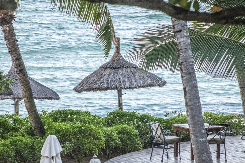 Vue vers la mer au-dessus du decking avec la table et des chaises avec des parapluies de paille photographie stock