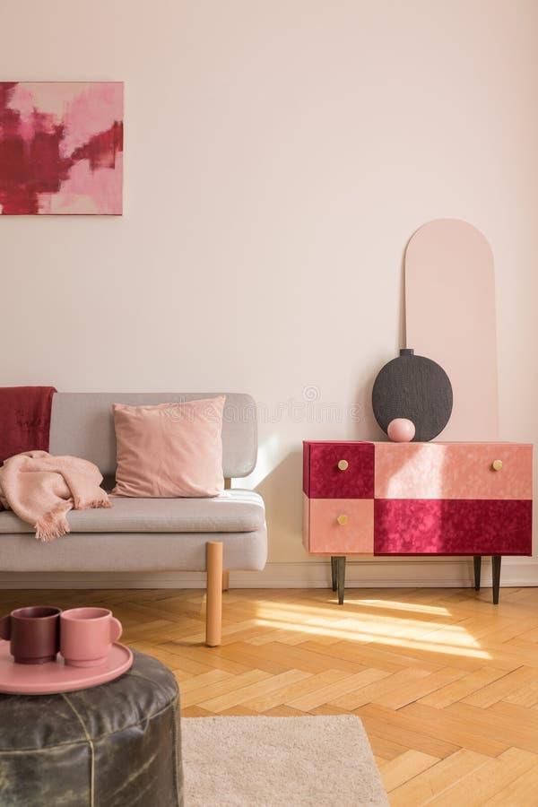 Vue verticale d'armoire couverte beau par suède avec le vase de fantaisie noir à côté du divan gris à la mode avec l'oreiller ros photos libres de droits