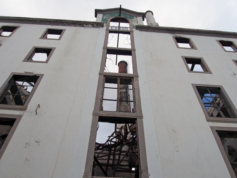 Vue verticale d'un grand bâtiment abandonné d'usine avec une cheminée grande évidente à l'intérieur des ruines image stock