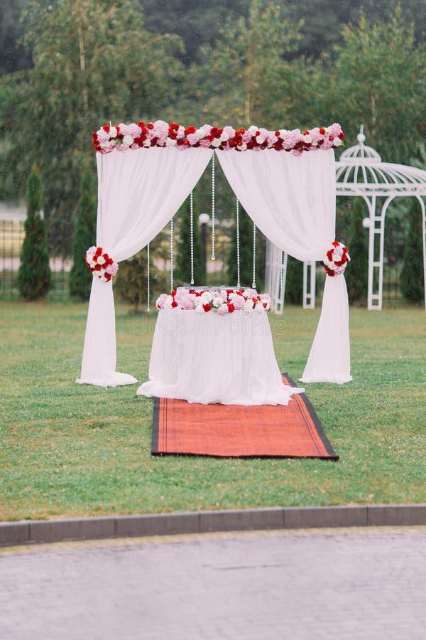 Vue verticale de la voûte de mariage décorée des roses rouges et blanches photo libre de droits
