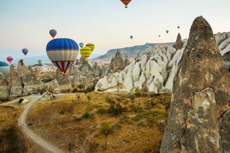 Vuelo colorido sobre las montañas - panorama de muchos globos del aire caliente de Cappadocia en la salida del sol Paisaje amplio imagenes de archivo