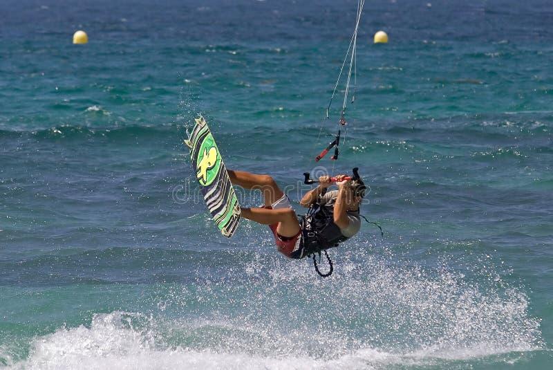 Vuelo de Kitesurfer a través del aire en una playa asoleada foto de archivo