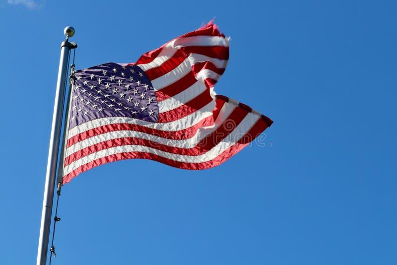 Vuelo de la bandera americana en brisa de la asta de bandera al aire libre imagen de archivo
