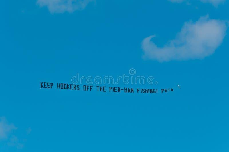 Vuelo de la bandera detrás de un aeroplano fotos de archivo