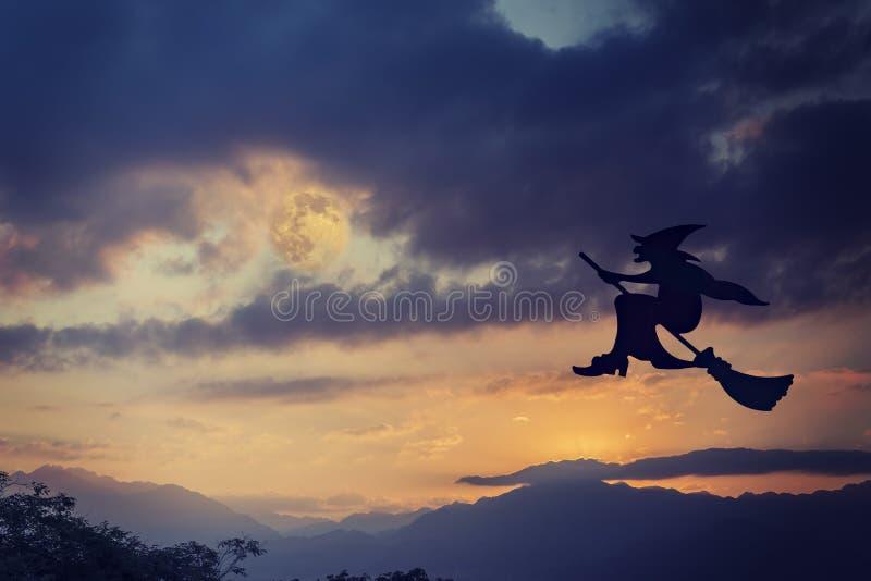 Vuelo de la bruja de Víspera de Todos los Santos en el palo de escoba imagen de archivo