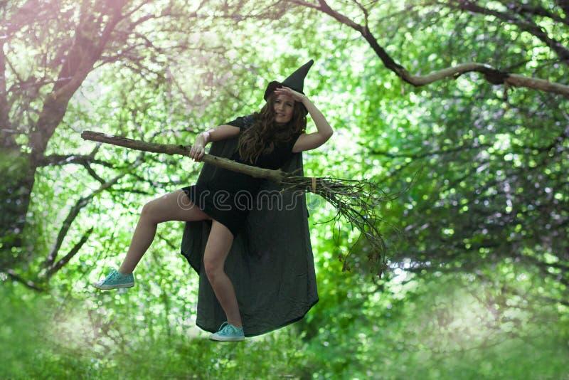 Vuelo de la bruja en una escoba Una muchacha atractiva imagen de archivo libre de regalías