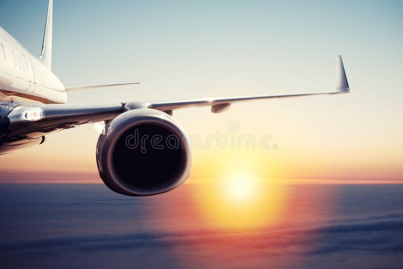 Vuelo de los aviones sobre las nubes durante salida del sol fotografía de archivo libre de regalías