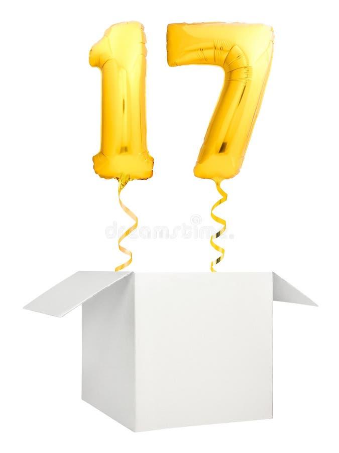 Vuelo de oro del globo del número diecisiete fuera de la caja blanca en blanco aislada en el fondo blanco imagen de archivo