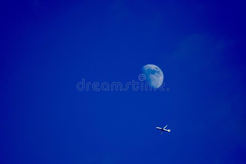 Vuelo del aeroplano debajo de la luna fotos de archivo libres de regalías