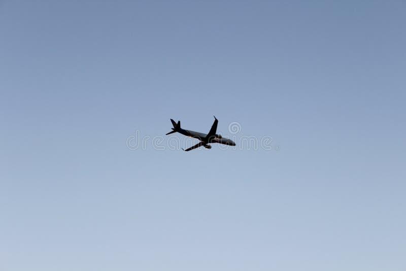 Vuelo del aeroplano en cielo de igualación azul marino Avión en fondo puro del cielo fotos de archivo