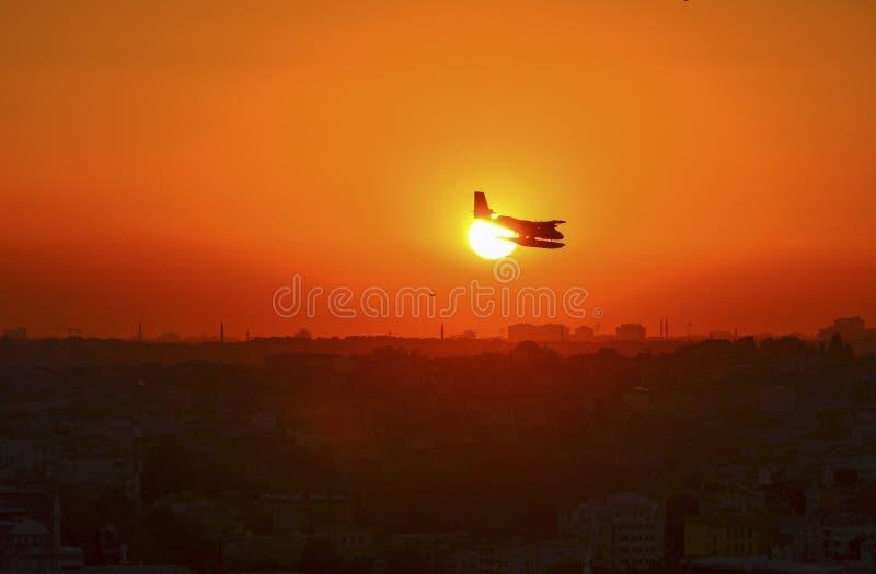 Vuelo del aeroplano sobre el mar tropical en la puesta del sol fotografía de archivo