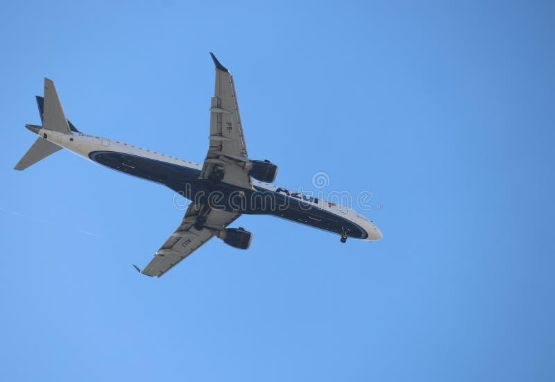 vuelo del aeroplano a trav?s del cielo urbano foto de archivo libre de regalías