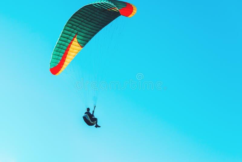 Vuelo del ala flexible en el paracaídas colorido en cielo claro azul en un día de verano soleado brillante Forma de vida activa,  fotografía de archivo