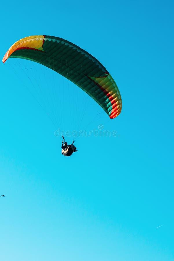 Vuelo del ala flexible en el paracaídas colorido en cielo claro azul en un día de verano soleado brillante Forma de vida activa,  foto de archivo