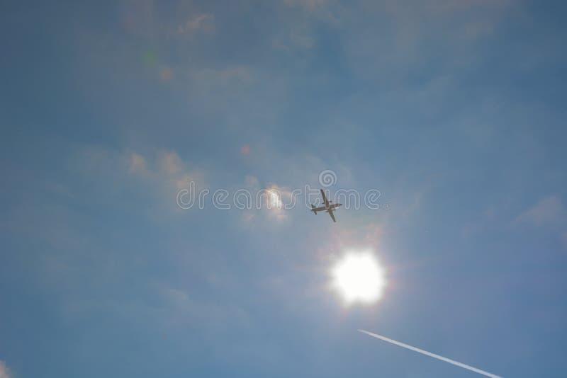 Vuelo del avión de aire delante del sol ardiente foto de archivo