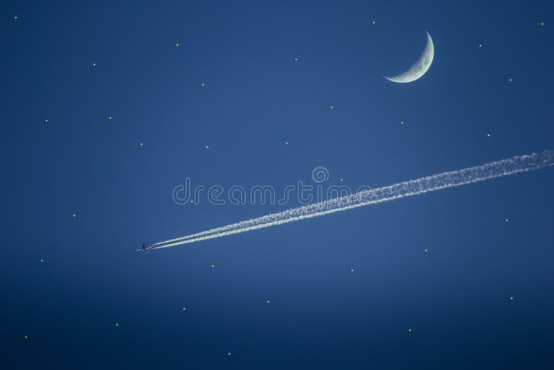 Vuelo del avión de reacción más allá de una media luna en el cielo azul foto de archivo libre de regalías