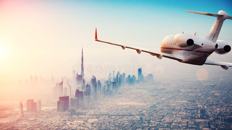 Vuelo del avión de reacción privada sobre la ciudad de Dubai en li hermoso de la puesta del sol fotografía de archivo