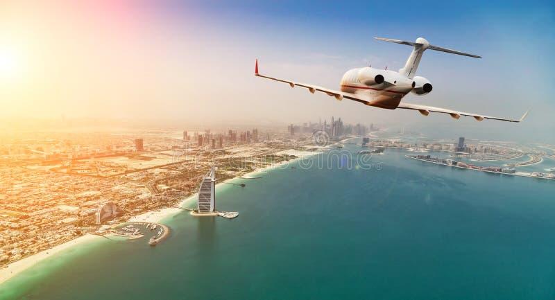 Vuelo del avión de reacción privada sobre la ciudad de Dubai en li hermoso de la puesta del sol fotografía de archivo libre de regalías