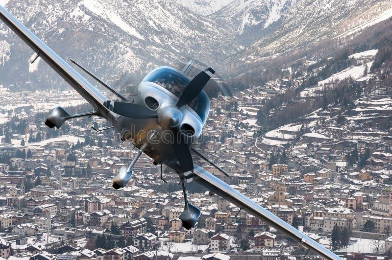 Vuelo del avión o de los aviones de Privat sobre la ciudad de vacaciones del invierno, pueblo rodeado por las montañas imagen de archivo libre de regalías