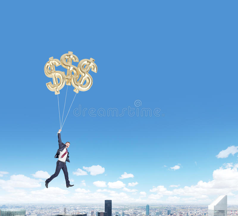 Vuelo del hombre con los globos del dólar sobre ciudad imágenes de archivo libres de regalías