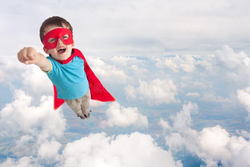 Vuelo del muchacho del niño del super héroe foto de archivo