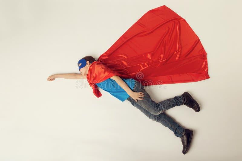Vuelo del niño del super héroe Muchacho del superhéroe en cabo rojo y máscara azul Copyspace, entonado fotografía de archivo libre de regalías