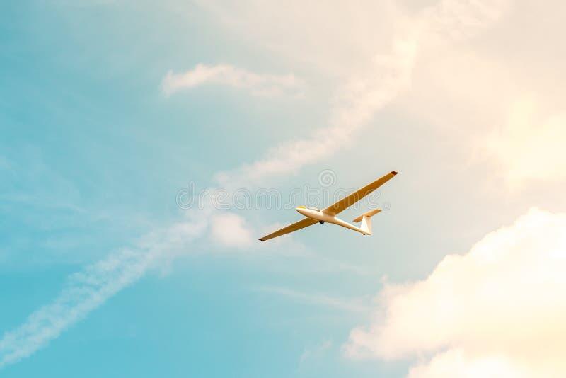 Vuelo del planeador contra el cielo azul con las nubes y la luz del sol foto de archivo libre de regalías