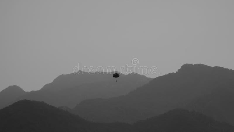 Vuelo del Skydiver con un fondo blanco y negro del paracaídas imagenes de archivo