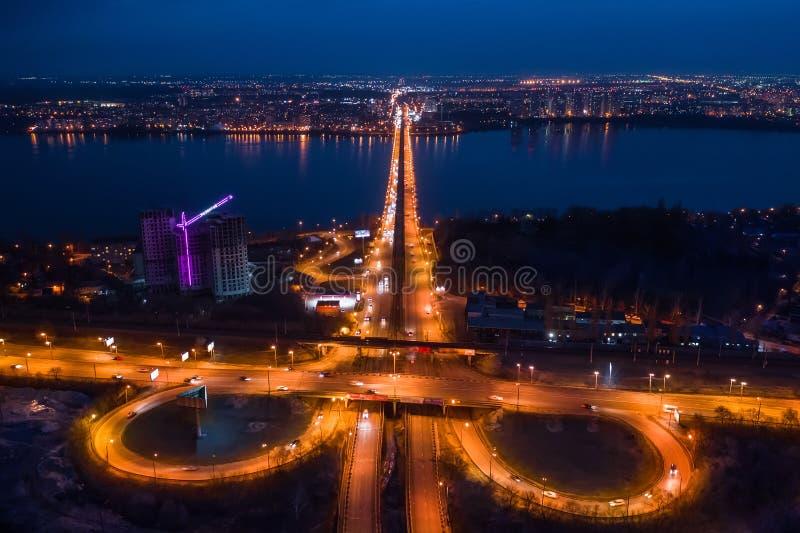 Vuelo en abejón sobre ciudad de la noche con el empalme del transporte, los caminos de ciudad del asfalto y los intercambios, vis foto de archivo