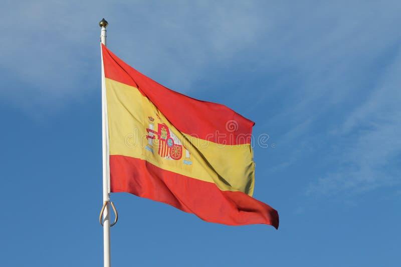 Vuelo español de la bandera contra el cielo azul marino fotografía de archivo libre de regalías