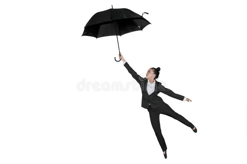 Vuelo femenino del empresario con un paraguas fotografía de archivo