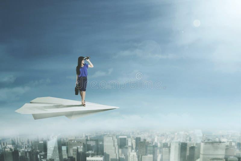 Vuelo joven de la empresaria con el avión de papel fotos de archivo