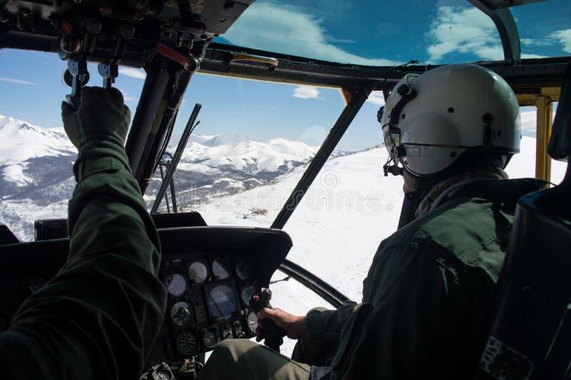 Vuelo militar del helicóptero a través de las montañas, del piloto blanco y del copiloto nevados llevando el flightsuit y la opin foto de archivo