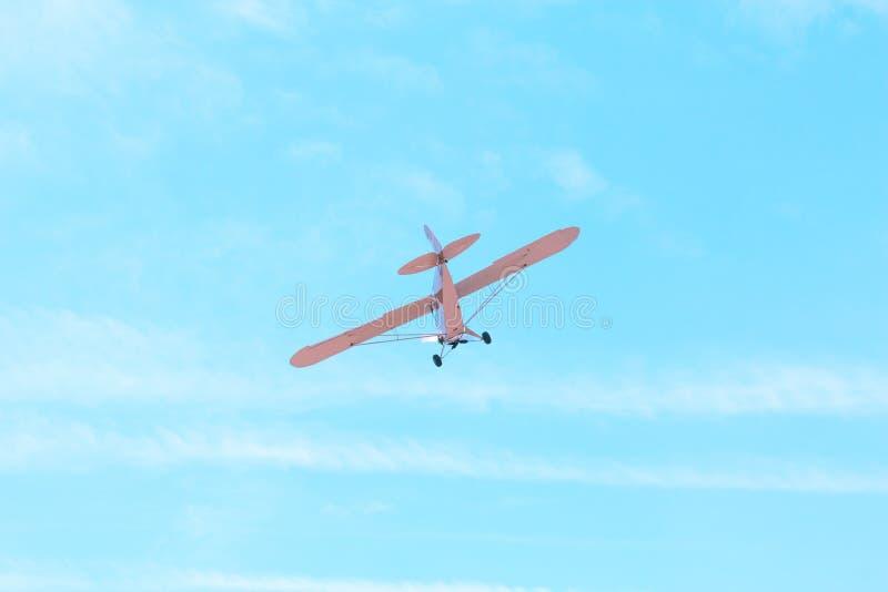 Vuelo plano del pequeño viejo vintage monomotor contra el cielo azul foto de archivo
