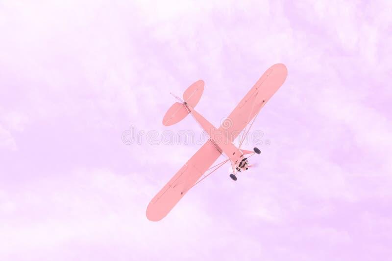 Vuelo plano del pequeño viejo vintage monomotor contra el cielo rosado, concepto de sueño, futuro feliz y perspectiva positiva el imágenes de archivo libres de regalías