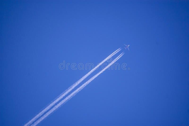 Vuelo plano en un cielo perfectamente azul con el rastro del vapor fotos de archivo libres de regalías