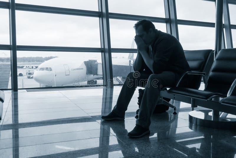 Vuelo retrasado que espera del hombre triste para imagen de archivo