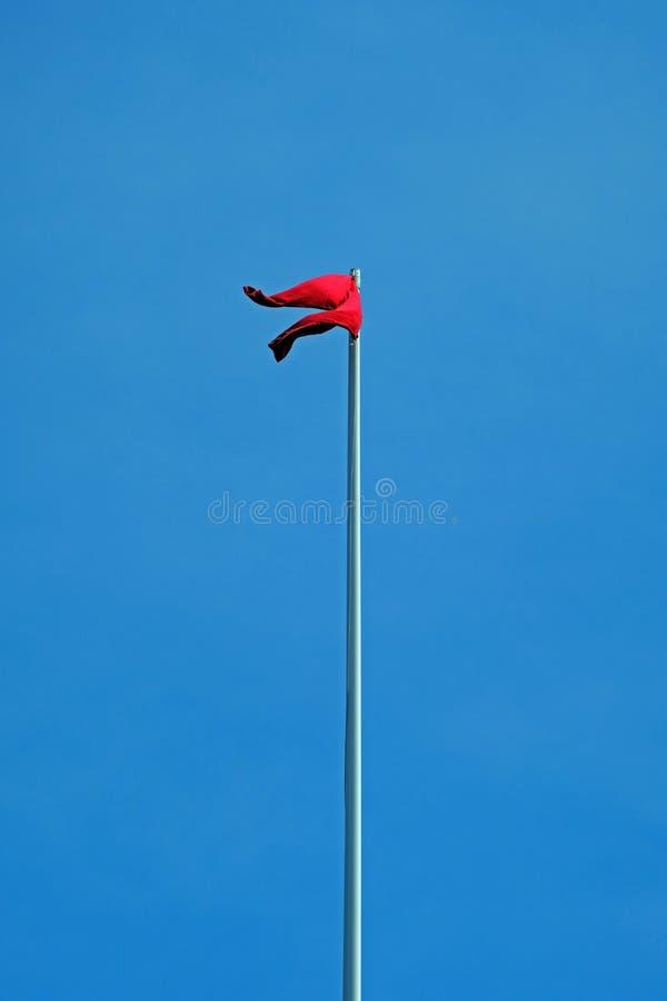 Vuelo rojo de los pantalones de una asta de bandera fotos de archivo