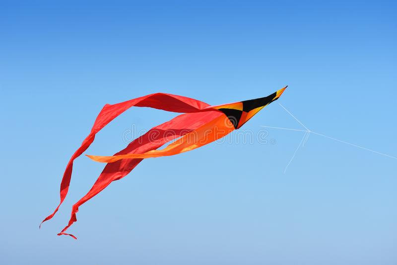 Vuelo rojo, negro y anaranjado de la cometa contra el cielo azul foto de archivo libre de regalías