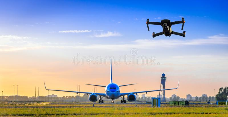 Vuelo sin tripulación del abejón cerca del aeroplano en el aeropuerto imagen de archivo libre de regalías