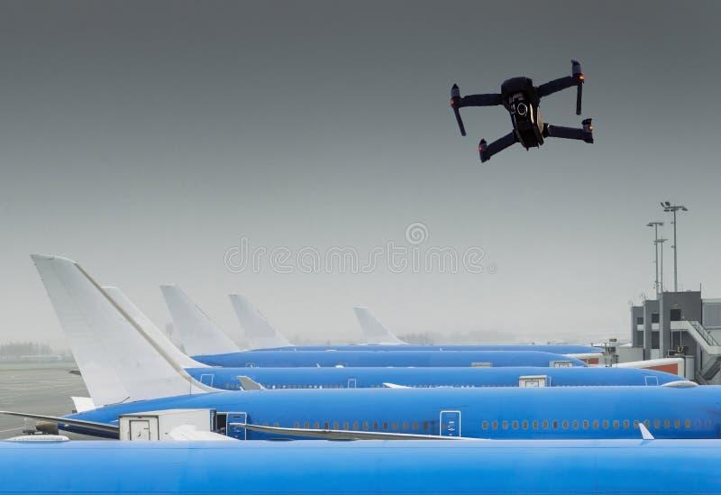 Vuelo sin tripulación del abejón cerca de la fila de aeroplanos comerciales en el aeropuerto fotos de archivo libres de regalías